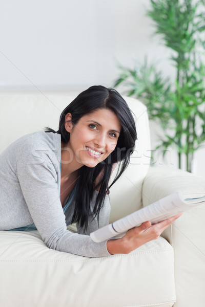 Woman holding a magazine as she lies on a sofa in a living room Stock photo © wavebreak_media
