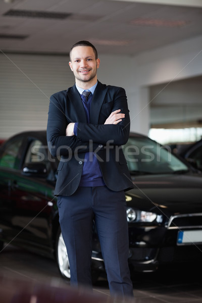 Salesman standing in front of car in a dealership Stock photo © wavebreak_media