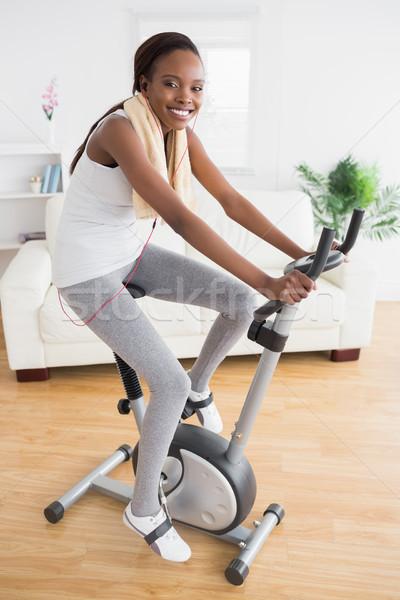 Black woman doing exercise bike with headphones in a living room Stock photo © wavebreak_media