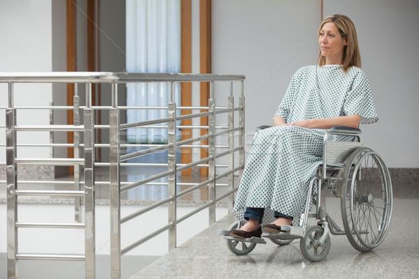 Woman wearing hospital gown and sitting in wheelchair in hospital corridor Stock photo © wavebreak_media