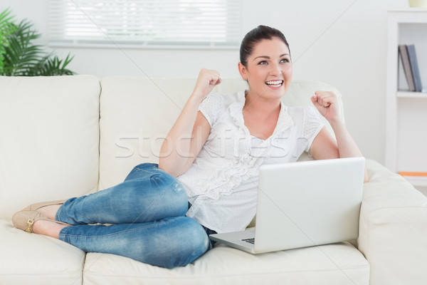 Lucky woman lying on the couch in a living room and using the laptop Stock photo © wavebreak_media