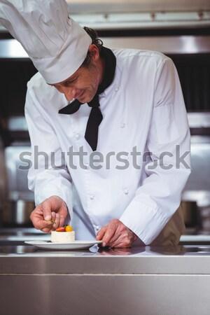 Chef cracking egg into bowl of flour in kitchen Stock photo © wavebreak_media