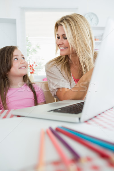 Woman is smiling at her daughter by the laptop in the kitchen Stock photo © wavebreak_media