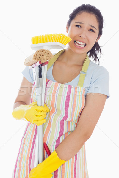 Distressed woman holding cleaing tools wearing an apron Stock photo © wavebreak_media