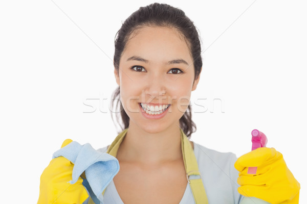 Smiling woman in rubber gloves with cloth and spray bottle Stock photo © wavebreak_media