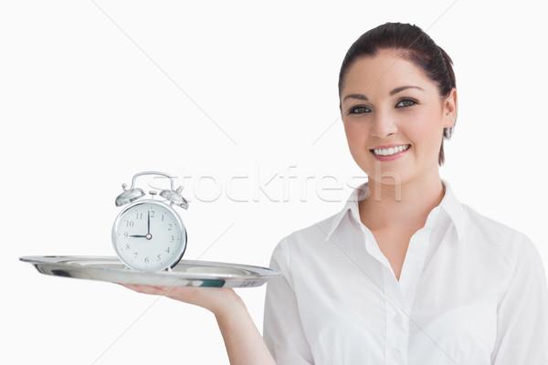 Smiling waitress holding alarm clock on a tray Stock photo © wavebreak_media
