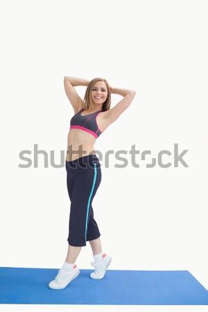 Portrait of happy woman posing on exercise mat Stock photo © wavebreak_media