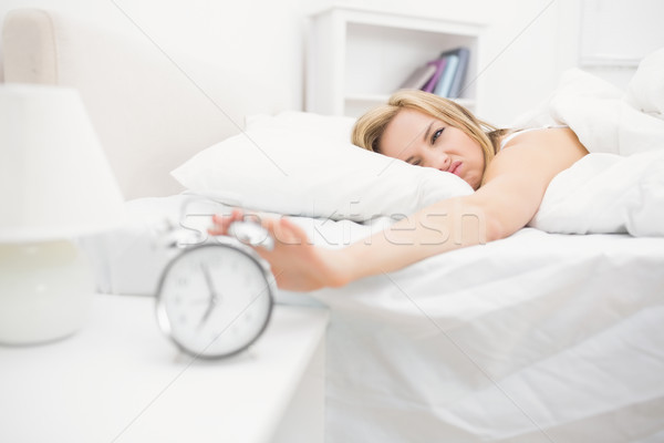Irritated woman in bed extending hand to alarm clock Stock photo © wavebreak_media