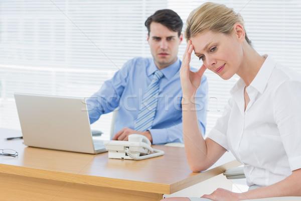 Upset businesswoman with man working on laptop Stock photo © wavebreak_media