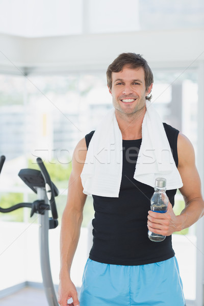 Smiling man holding water bottle at spinning class in bright gym Stock photo © wavebreak_media