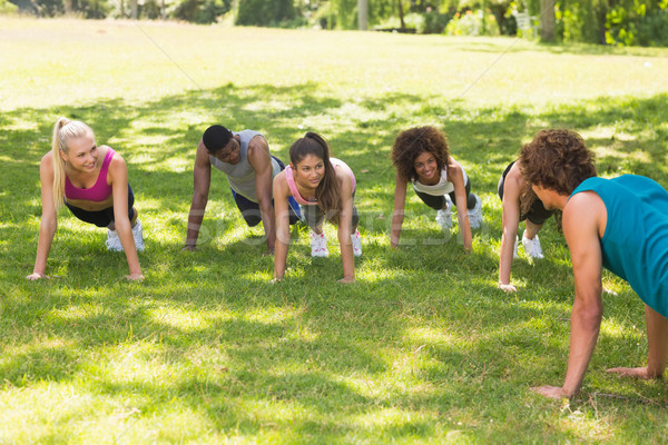 Instructor fitness clase flexiones parque grupo Foto stock © wavebreak_media