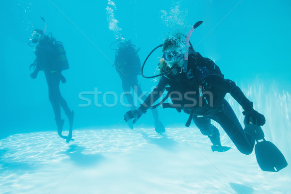 Friends on scuba training submerged in swimming pool one looking Stock photo © wavebreak_media