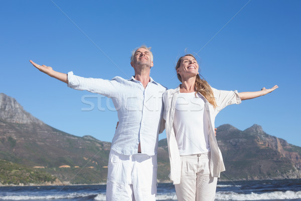 Happy couple standing with arms outstretched at the beach Stock photo © wavebreak_media