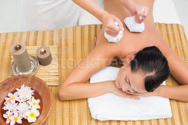 Peaceful brunette enjoying a herbal compress massage Stock photo © wavebreak_media