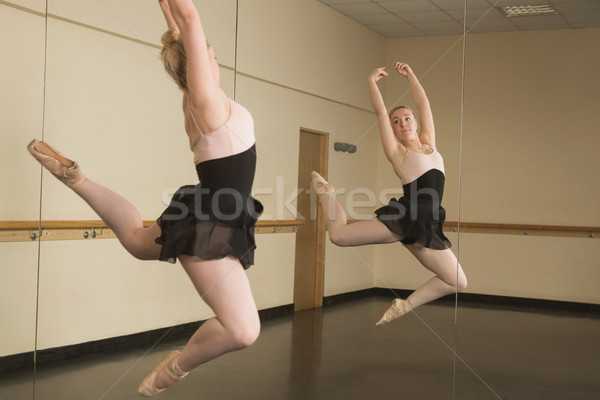 Stock photo: Beautiful ballerina dancing in front of mirror