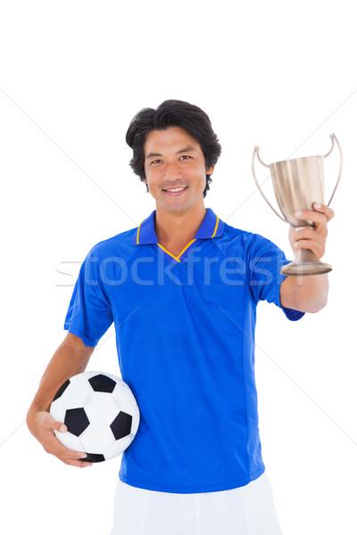 Football player in blue holding winners cup Stock photo © wavebreak_media