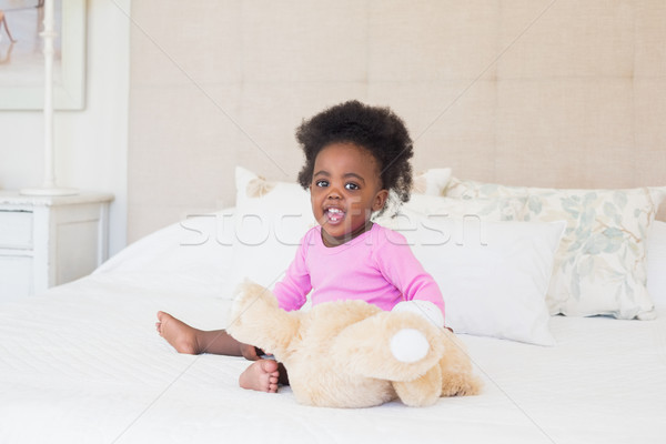 Stock photo: Baby girl in pink babygro sitting on bed