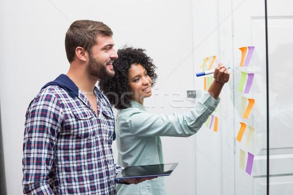 Team looking at sticky notes on window Stock photo © wavebreak_media