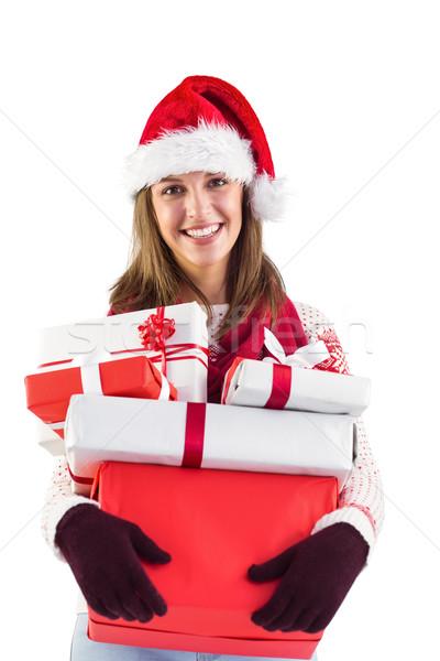 Festive brunette with santa hat holding many gifts Stock photo © wavebreak_media