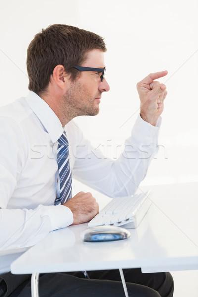 Businessman sitting at his desk pointing something Stock photo © wavebreak_media