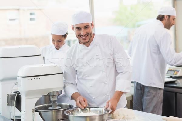 Szczęśliwy piekarz uśmiechnięty kamery kuchnia piekarni Zdjęcia stock © wavebreak_media