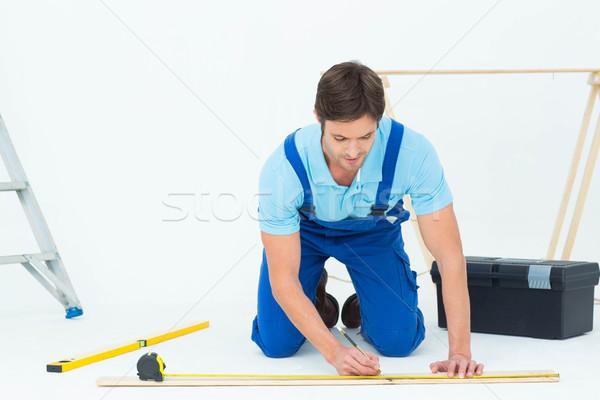 Worker marking on wood while measuring Stock photo © wavebreak_media