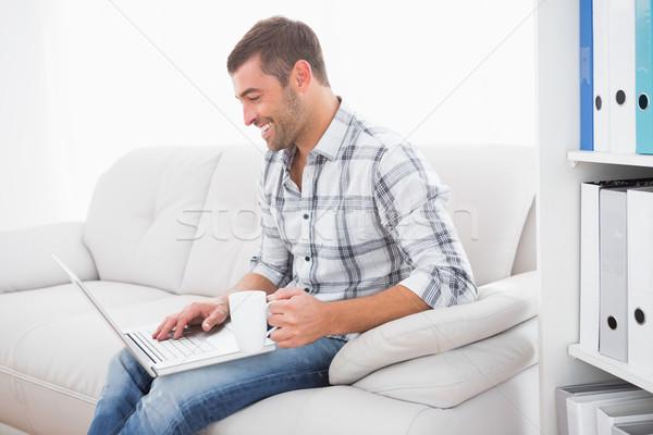 Lächelnd Mann mug mit Laptop Sitzung Sofa Stock foto © wavebreak_media
