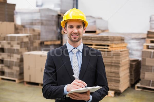 Uśmiechnięty magazynu kierownik piśmie schowek człowiek Zdjęcia stock © wavebreak_media
