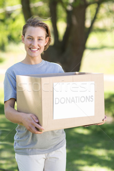 Happy volunteer in the park holding box Stock photo © wavebreak_media