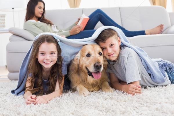Happy siblings with dog under blanket Stock photo © wavebreak_media