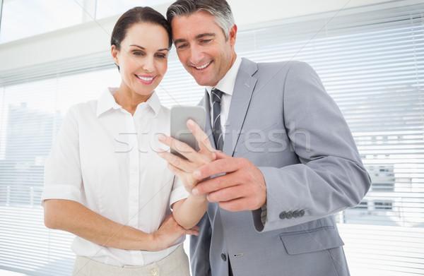 Employee showing co worker her phone Stock photo © wavebreak_media