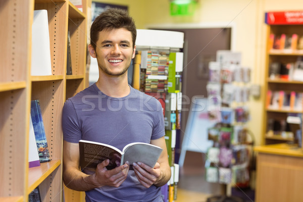 Smiling university student holding textbook Stock photo © wavebreak_media