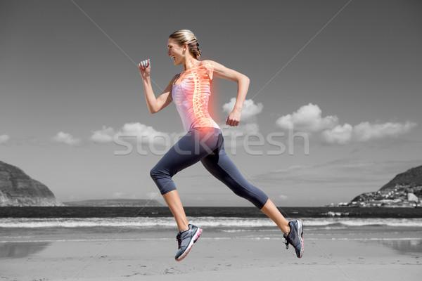 Highlighted back bones of jogging woman on beach Stock photo © wavebreak_media