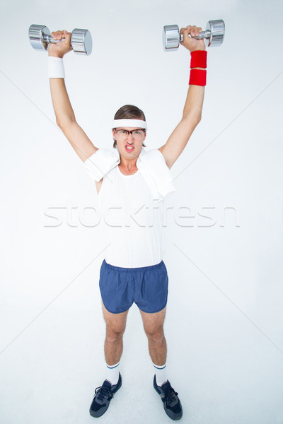 Geeky hipster lifting dumbbells in sportswear Stock photo © wavebreak_media