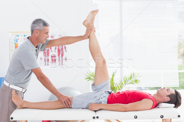 Physiotherapist doing leg stretching to his patient Stock photo © wavebreak_media