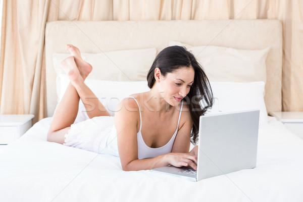 Pretty brunette browsing on bed Stock photo © wavebreak_media