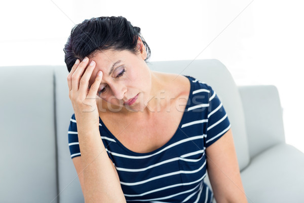 Unhappy woman sitting on the couch Stock photo © wavebreak_media