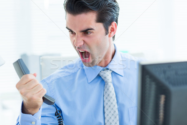 Businessman shouting as he holds out phone at office Stock photo © wavebreak_media