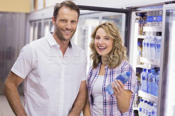 Retrato sorridente casual casal garrafa de água supermercado Foto stock © wavebreak_media