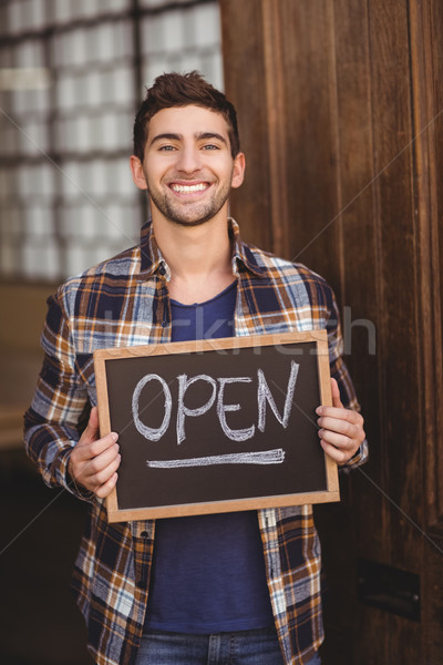 Smiling casual waiter showing chalkboard with open sign Stock photo © wavebreak_media