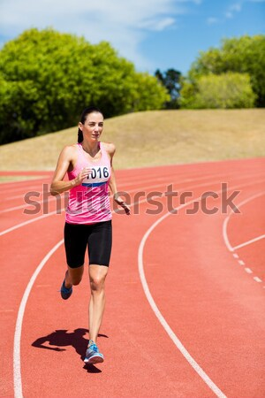 Digital composite image of sport runner running on tracks against city Stock photo © wavebreak_media