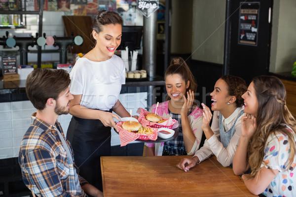 Waitress serving burgers to customers in restaurant Stock photo © wavebreak_media