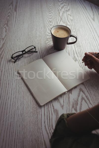 Businesswoman writing on book at office desk Stock photo © wavebreak_media