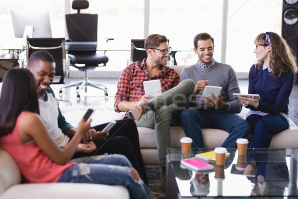 Smiling business people sitting on sofa Stock photo © wavebreak_media