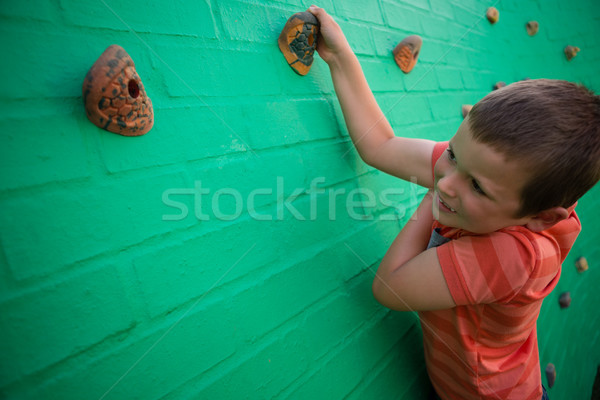 Elementary boy climbing on brick wall Stock photo © wavebreak_media