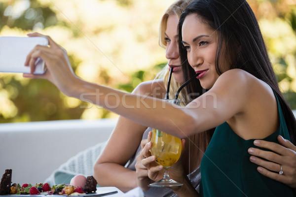 Stock photo: Female friends taking selfie while having drinks