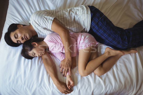 Father and daughter sleeping together in bedroom Stock photo © wavebreak_media