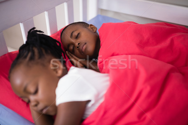 Brother and sister sleeping on bed at home Stock photo © wavebreak_media