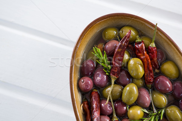 Pickled olives with herbs and chili in bowl on table Stock photo © wavebreak_media