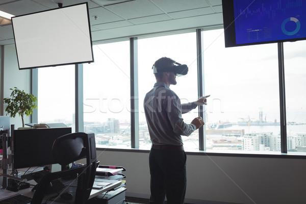 Businessman using virtual reality glasses against glass windows Stock photo © wavebreak_media